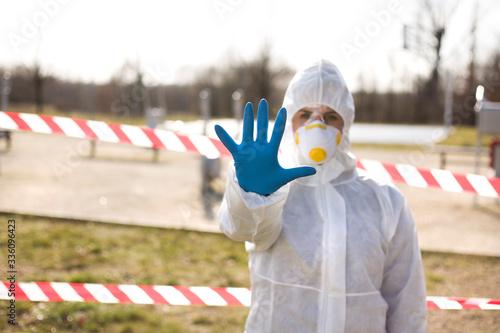Obraz Kobieta w stroju ochronnym powstrzymuje dłonią przed wejściem do parku - fototapety do salonu