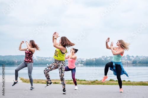 Fototapeta A group of young women, wearing colorful sports outfits, doing zumba exercises outside by city lake. Dancing training to loose weight in summer. Healthy lifestyle concept. Female sport leisure. obraz