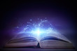 canvas print picture - Open book with magic glowing on table. Fairy tale