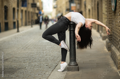Photo an athletic woman ding a back bend in the street
