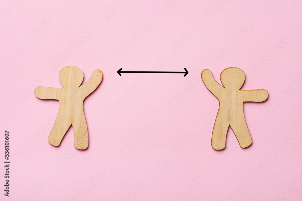 Fototapeta keep distance concept, two wooden people on pink background, preventive measures, infection control