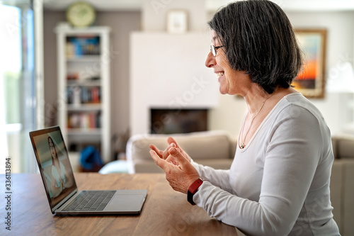 Adult  woman having video chat online on laptop with her granddaughter at home during quarantine isolation pandemic Canvas