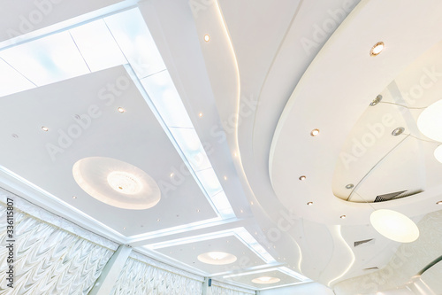 Obraz suspended ceiling with halogen spots lamps and drywall construction in empty room in apartment or house. Stretch ceiling white and complex shape. - fototapety do salonu