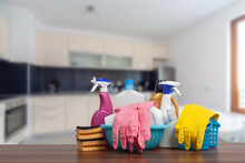 Home Cleaning Service Concept With Supplies. Close Up Of Cleaning Supplies In Front Of Kitchen.