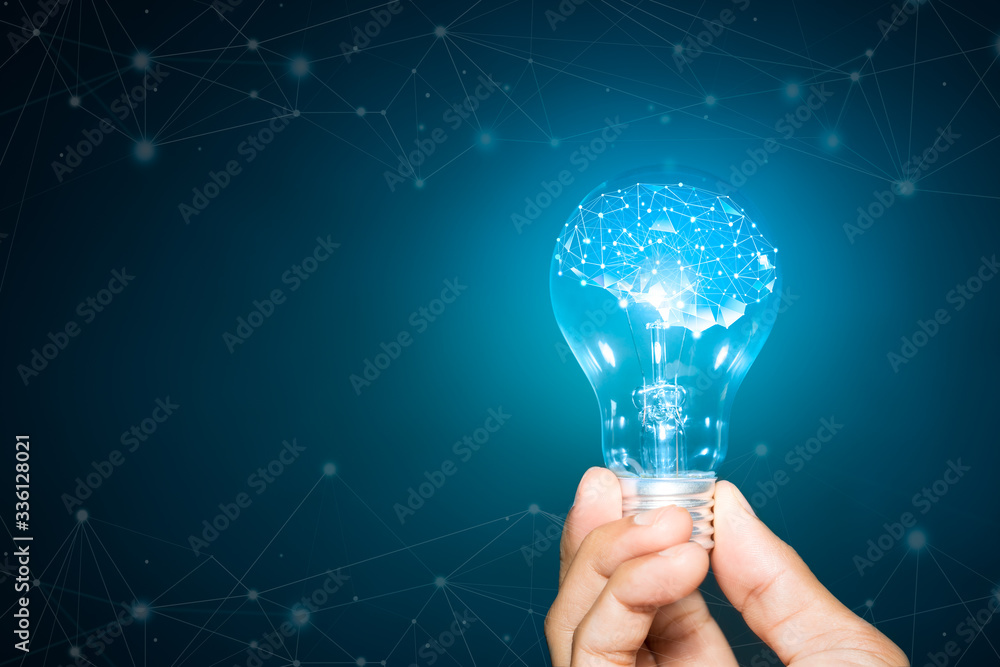 Fototapeta light bulb hold in hand on blue background, Brain with shining wireframe, Neural networks and artificial intelligence