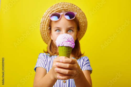 Obraz na plátne Funny caucasian child girl with ice cream, close-up shot on yellow isolated background