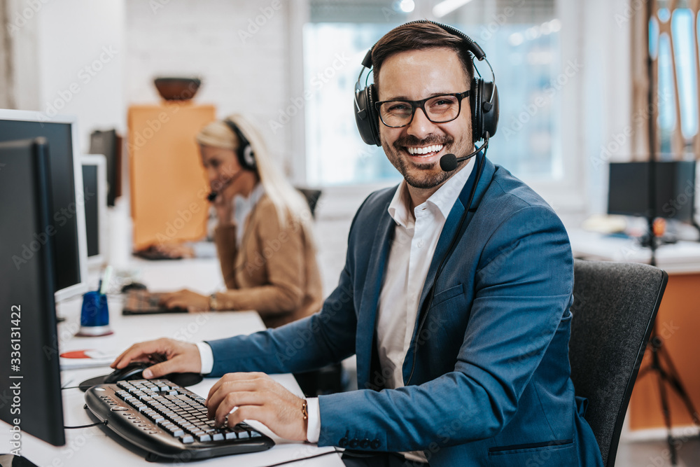 Fototapeta Handsome male customer service agent working in call center office as a telemarketer.
