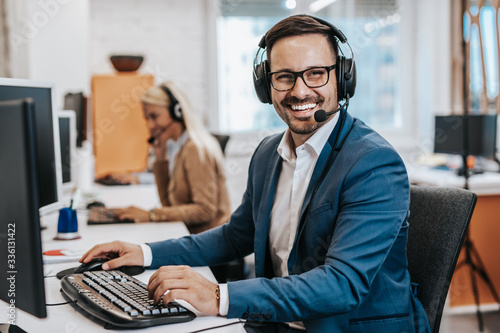 Obraz Handsome male customer service agent working in call center office as a telemarketer. - fototapety do salonu