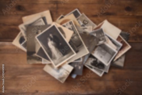old vintage monochrome photographs in sepia color are scattered on a wooden tabl Canvas