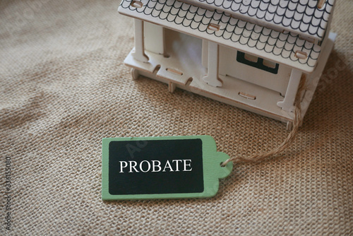 Photo A toy wooden house on a rugs with a wooden tag written with word Probate