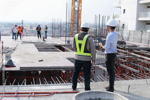 Obraz Two engineers work on the construction site. They are checking the progress of the work. - fototapety do salonu
