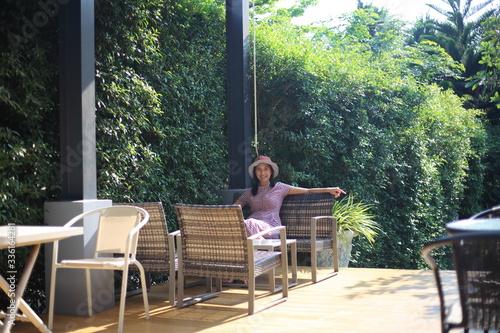 Fotografie, Tablou Woman sitting in a green garden
