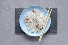Close Up. Asian Oriental Cuisine. Fungose Glass Rice Noodles With Vegetables, Pepper And Herbs In A Blue Plate With Bamboo Sticks On A Gray Neutral Background.