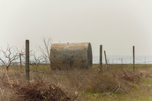 Abandoned Rusty Water Tank On The Field