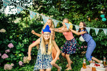 Happy Girls Doing A Conga Line On A Birthday Party Outdoors