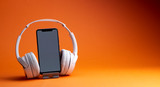 White headphones with smartphone mockup, isolate on orange, music online concept.