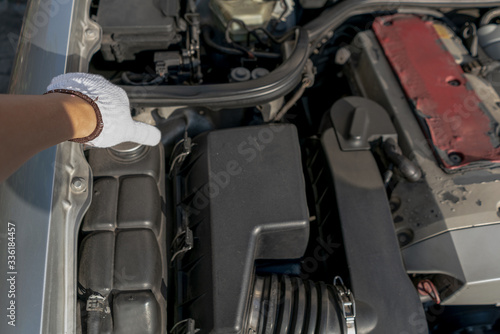 Mechanic or car owner close or open radiator expansion or coolant reservoir cap to check heat transfer fluid level for protect engine from over heat Canvas Print