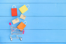 Online Shopping / E-commerce And Customer Experience Concept : Shopping Cart With Boxes, Colored Shopping Bags On Floor, Depicts Consumers / Buyers Buy Or Purchase Goods And Service From Home