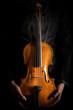Alte Geige mit Bogen auf schwarzem Hintergrund.