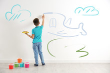 Little Child Drawing Plane On White Wall Indoors