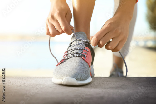 Sporty woman tying shoelaces outdoors on sunny day, closeup Poster Mural XXL