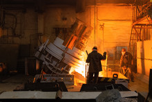 Foundry Workers Pouring Metal From Furnace