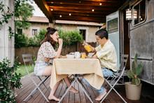 Young Couple Having Breakfast Near Caravan