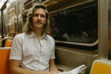 Man With Long Curly Blonde Hair And Mustache Sitting And Reading On The Subway