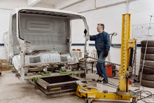Repairman Lifting Vehicle Body
