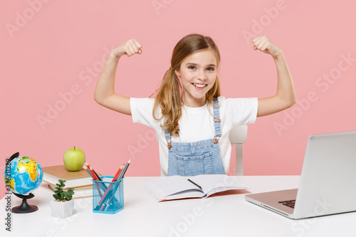 Smiling little kid schoolgirl 12-13 years old sit study at white desk with pc laptop isolated on pink background Wallpaper Mural