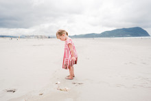 Little Girl Explores The Beach In Classic Linen Dress With Red Stripes With Foot Prints Behind Her