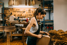 Young Woman Luthier Working In...
