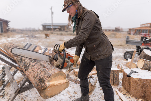 Ranch Manager and Cowgirl  cutting wood with a chainsaw - 336222049