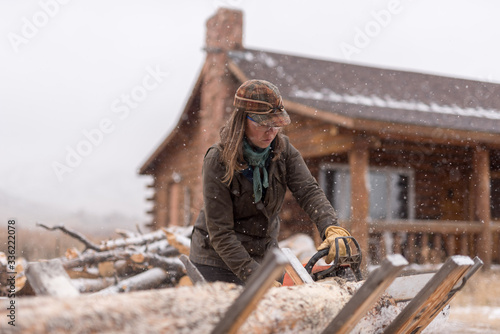 Ranch Manager and Cowgirl  cutting wood with a chainsaw - 336222078