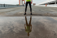 Reflection Of Sportsman In Puddle