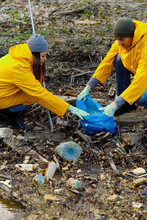 A Man And A Woman Clean The Reservoir Of Plastic And Garbage.