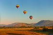 canvas print picture - Hot air balloons with tourists above the Pilanesberg reserve. Three hot air balloons, decorated safari motifs against blue sky, mountains on background. Holiday Safari in South Africa.