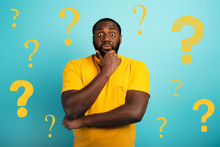 Confuse And Pensive Expression Of A Boy With Many Questions . Cyan Colored Background