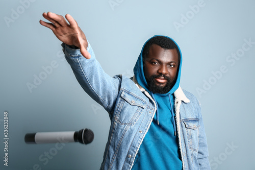 Male African-American singer dropping microphone on color background Tableau sur Toile