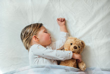 Toddler Baby Sleeping On White Sheets Hugging Soft Brown Teddy Bear. Children's Nap Time Or Bedtime. Child Sleep Deprivation. Child Sleep Routine And Schedule.  Top View.