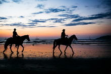Silhouette Of Two People Riding Horses On The Beach At Sunset