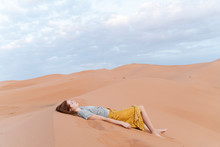 Young Woman Lying In Sand Dune...