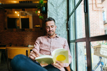 Man Reading Book In A Cafe At ...