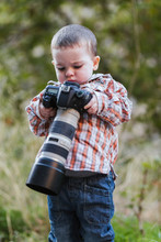 Portrait Of Toddler Looking At Digital Reflex Camera With Big Lens In Nature