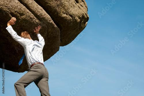 Strong businessman struggling to lift massive boulder into blue sky copy space Canvas Print