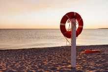 An Orange Life Buoy On A Sunset Beach Background. Picturesque Sea Sunset. Saving Life Concept. Dreaming About Sea Concept. Sos Concept.