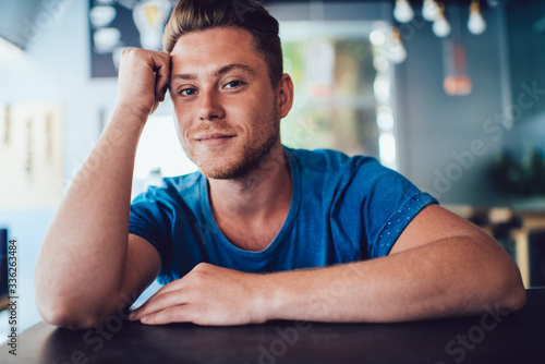 Portrait of handsome caucasian man with blue eyes and in good looking casual t-shirt resting in cafe interior dreaming, young blonde 20s hipster guy looking at camera sitting at table pondering Tableau sur Toile