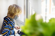 canvas print picture - Sad little boy looking into window during coronavirus pandemic. Child boring without communication and walking. Stay at home while quarantine.