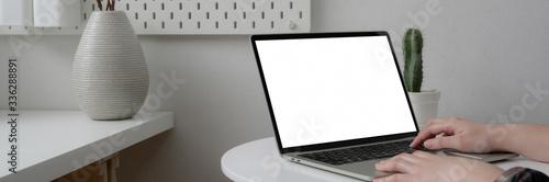 Obraz Cropped shot of female freelancer working on blank screen laptop on white circle table - fototapety do salonu