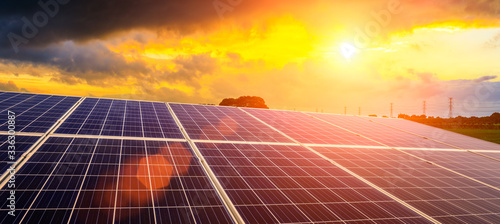 Fotografiet Photovoltaic solar panels and high voltage power lines at sunset sky background,green clean alternative energy